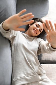 Vista superior de uma jovem sorridente relaxando em um sofá