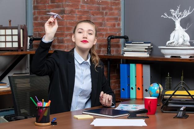Vista superior de uma jovem trabalhadora de escritório sentada em sua mesa jogando avião de papel