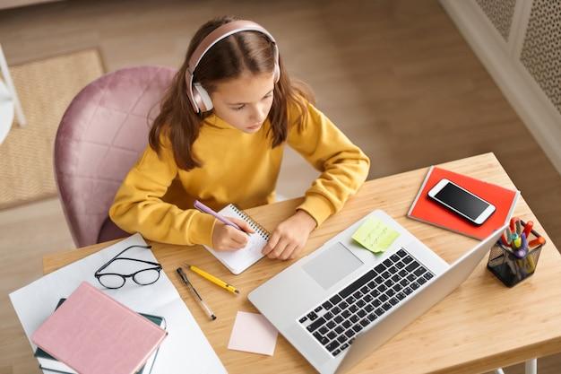 Vista superior de uma jovem usando fones de ouvido, fazendo lição de casa na mesa de trabalho do quarto
