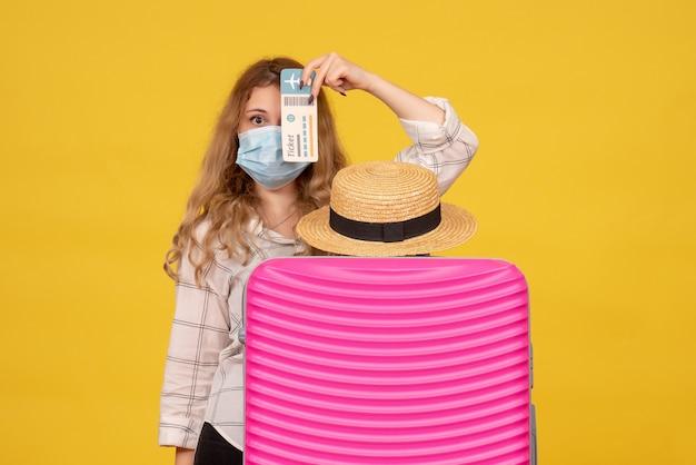 Vista superior de uma jovem usando máscara, mostrando o ingresso e em pé atrás de sua bolsa rosa