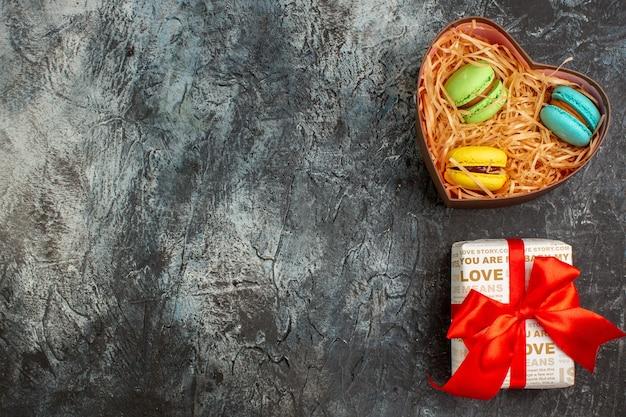 Vista superior de uma linda caixa de presente amarrada com fita vermelha e deliciosos macarons no lado esquerdo em um fundo escuro e gelado
