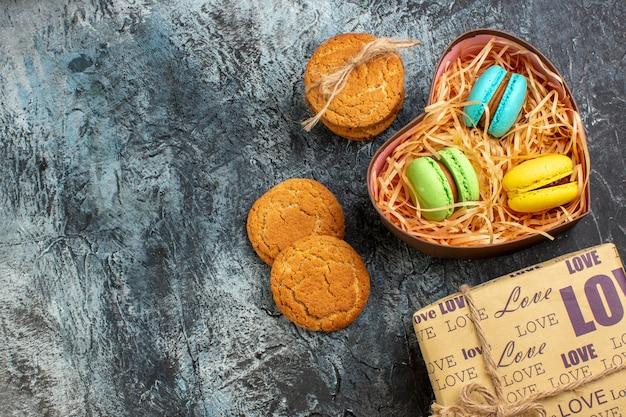 Vista superior de uma linda caixa de presente com macarons e biscoitos no lado esquerdo em um fundo escuro de gelo