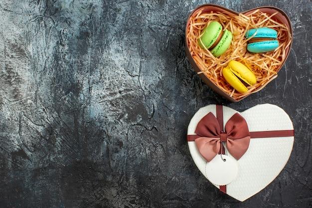 Vista superior de uma linda caixa de presente em forma de coração com deliciosos macarons no lado esquerdo em um fundo escuro e gelado