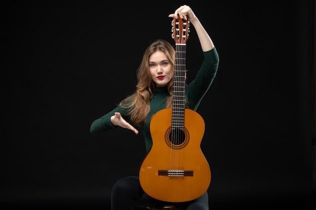 Vista superior de uma linda garota loira músico segurando violão e dando as boas-vindas a alguém no escuro