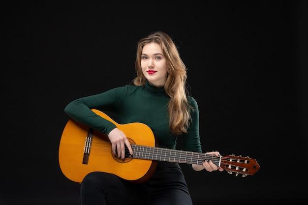 Vista superior de uma linda garota loira tocando guitarra no preto