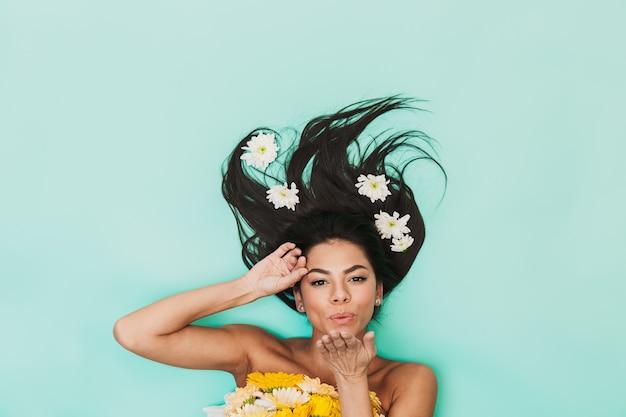 Vista superior de uma linda jovem morena com cabelo comprido deitado sobre o azul, segurando um buquê de flores