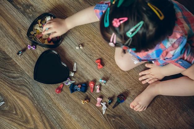 Vista superior de uma linda menina brincando com a coleção de grampos de cabelo sentada em um chão de madeira em casa