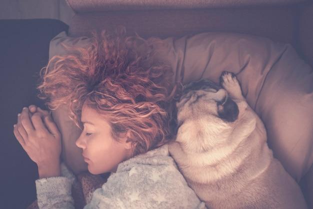 Vista superior de uma linda mulher dormindo com seu melhor amigo, cão afetivo, pug - conceito de amor e amizade com pessoa e animais - protectoipn e amigos para sempre juntos em casa pelo resto da vida