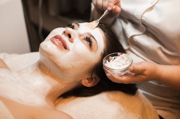 Vista superior de uma linda mulher encostada em uma cama de spa com os olhos abertos enquanto faz a máscara branca de cuidados com a pele em um spa resort.