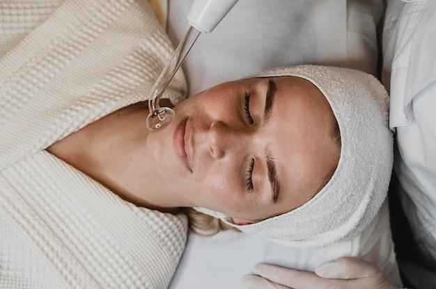 Vista superior de uma linda mulher recebendo tratamento facial