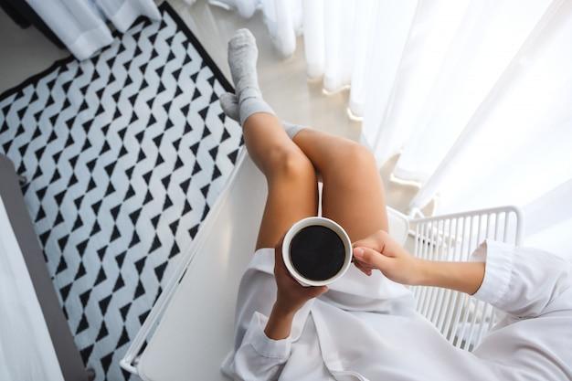 Vista superior de uma linda mulher tomando café quente no quarto em casa de manhã