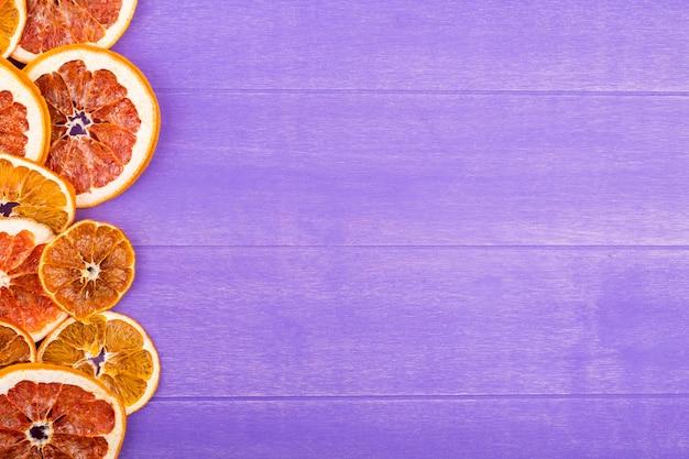 Vista superior de uma linha de fatias secas de laranja e toranja, dispostas no lado no fundo de madeira roxo com espaço de cópia
