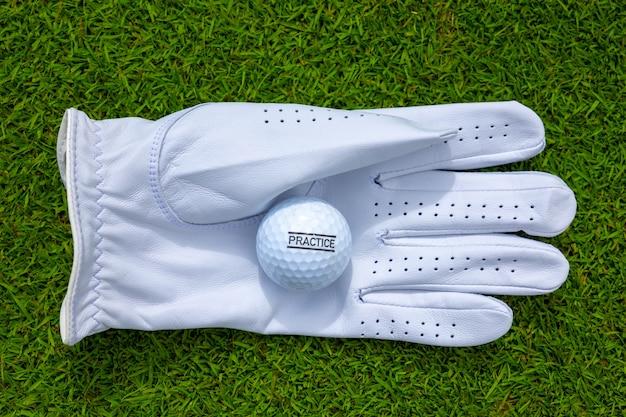 Vista superior de uma luva de golfe branca com uma bola de golfe em um campo gramado