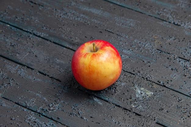 Vista superior de uma maçã amarela-avermelhada sobre uma mesa de madeira cinza