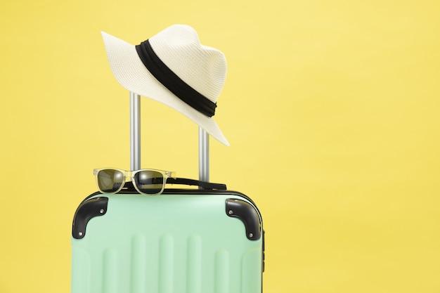 Vista superior de uma mala, óculos de sol, câmera e chapéu em um fundo amarelo - conceito de férias