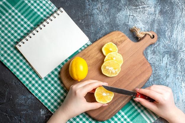 Vista superior de uma mão cortando limões frescos em uma tábua de madeira e um caderno em tecido verde despojado