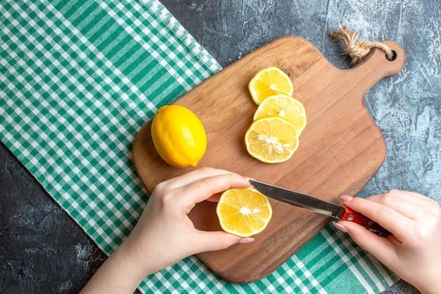 Vista superior de uma mão cortando limões frescos em uma tábua de madeira em fundo escuro