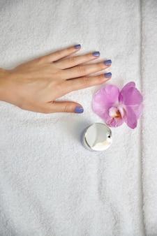 Vista superior de uma mão feminina com unhas cobertas com esmalte perto do frasco de cosmético e flores frescas