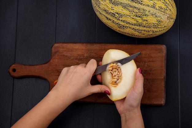 Vista superior de uma mão feminina cortando melão amarelo com faca na placa de madeira da cozinha no preto