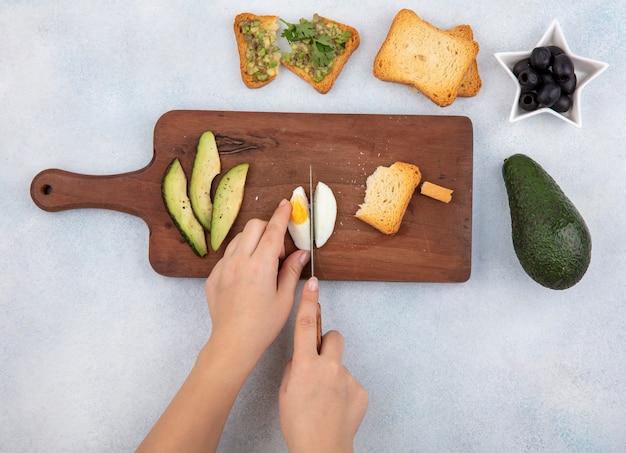 Vista superior de uma mão feminina cortando ovo cozido em fatias na placa de madeira da cozinha com fatias de abacate torradas, fatia de pão azeitonas pretas no branco