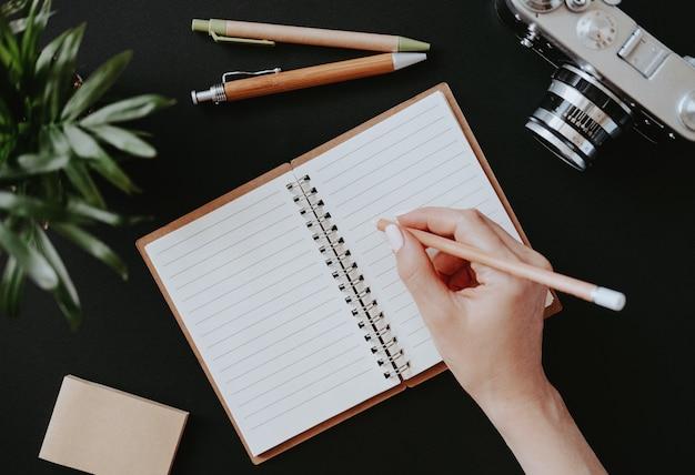 Vista superior de uma mão feminina deitada plana escreve notas em um caderno aberto sobre uma mesa preta ao lado de canetas coloridas com papel e uma câmera de filme