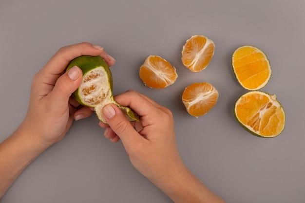 Vista superior de uma mão feminina descascando tangerina verde fresca