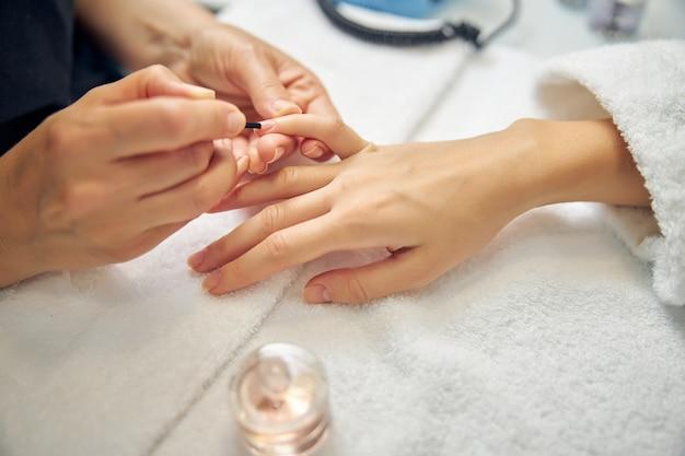 Vista superior de uma mão feminina enquanto a manicure as aplica antes de pintar