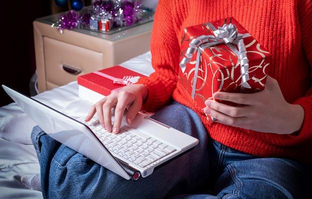 Vista superior de uma mão feminina segurando uma caixa de presente e digitando texto no laptop