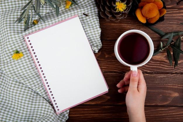 Vista superior de uma mão segurando uma caneca de chá com caderno na madeira