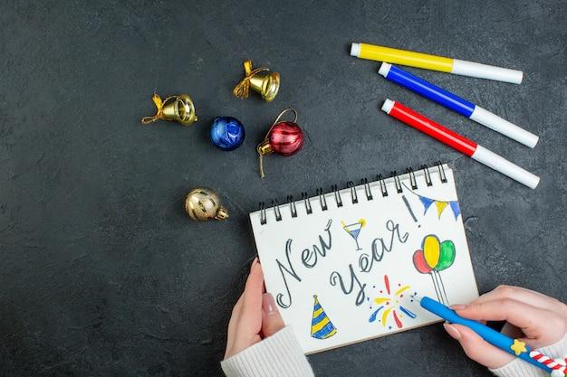 Vista superior de uma mão segurando uma caneta no caderno espiral com acessórios de decoração e escrita de ano novo em fundo preto