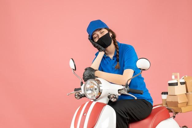 Vista superior de uma mensageira sonolenta usando máscara médica e luvas, sentada na scooter, entregando pedidos em pêssego pastel