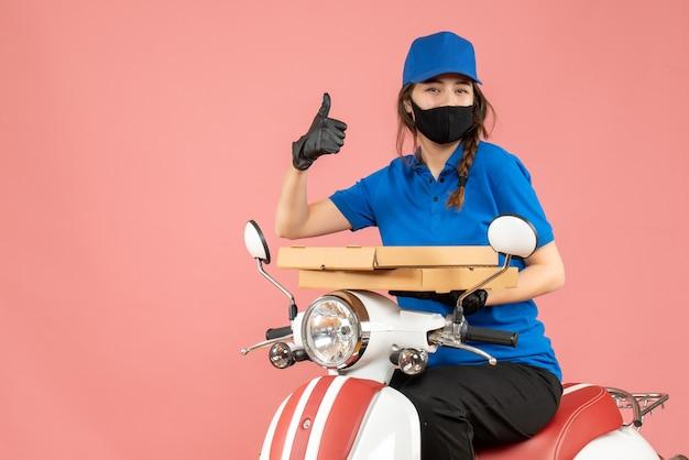 Vista superior de uma mensageira sorridente, usando máscara médica e luvas, sentada na scooter, entregando pedidos, fazendo um gesto de aprovação em pêssego