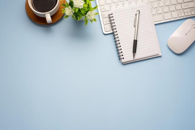 Vista superior de uma mesa azul com equipamentos de trabalho colocados no escritório. copie o espaço.