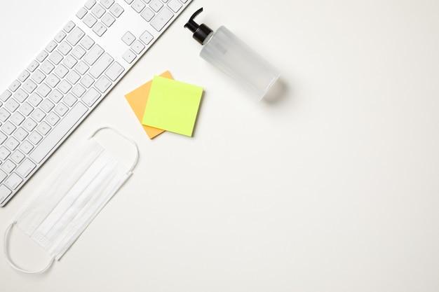 Vista superior de uma mesa branca com um teclado, uma máscara cirúrgica branca, dois adesivos coloridos de lembrete e um distribuidor de bomba de álcool gel