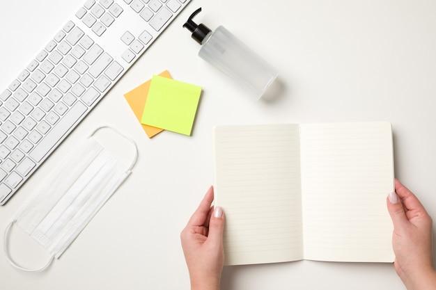 Vista superior de uma mesa branca com um teclado, uma máscara cirúrgica branca, dois adesivos coloridos de lembrete, um dispensador de bomba de álcool gel e mãos femininas segurando um caderno em branco.