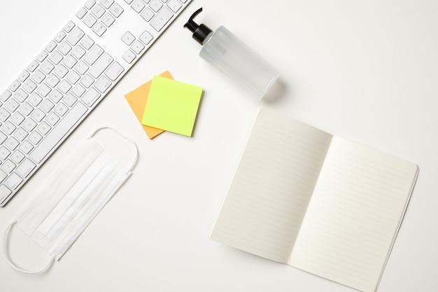 Vista superior de uma mesa branca com um teclado, uma máscara cirúrgica branca, dois adesivos coloridos de lembrete, um distribuidor de bomba de álcool gel e um bloco de notas em branco aberto