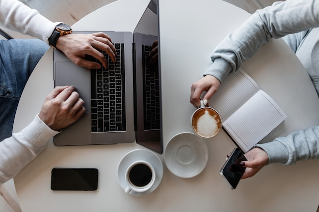 Vista superior de uma mesa branca onde está sentado um homem com um laptop e uma mulher com um bloco de notas e um telefone celular com uma xícara de café