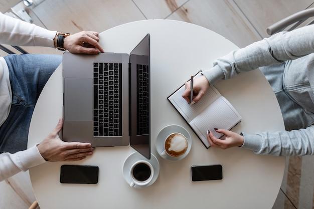 Vista superior de uma mesa branca onde está sentado um homem de negócios com um laptop e uma freelancer feminina com um bloco de notas com um telefone celular com uma xícara de café