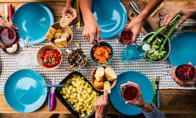 Vista superior de uma mesa cheia de comida e amigos desfrutando do evento juntos - pratos azuis e fundo colorido - conceito sem restrições de família e amigos do coronavírus