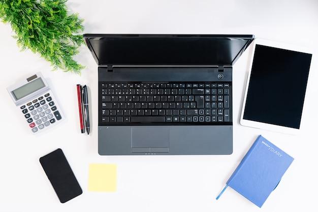 Vista superior de uma mesa de escritório branca com um laptop, calculadora, telefone celular, post-it, canetas, caderno, tablet, tudo em boa luz