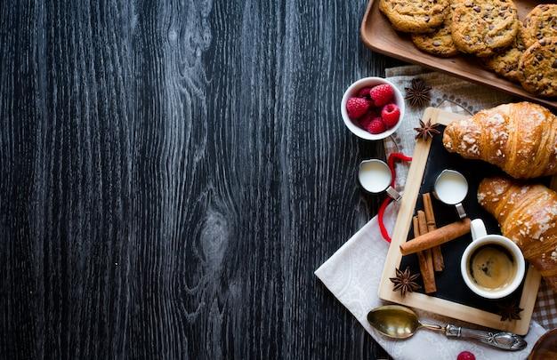 Vista superior de uma mesa de madeira cheia de bolos, frutas, café, biscoitos, especiarias e muito mais