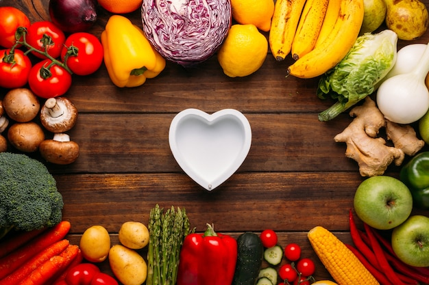 Vista superior de uma mesa de madeira cheia de vegetais e no meio da imagem um coração vazio