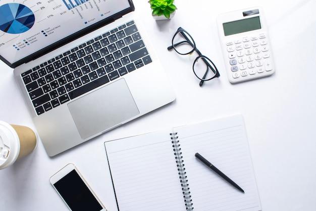 Vista superior de uma mesa de mulher de negócios com informações de conta financeira em um laptop em uma mesa branca