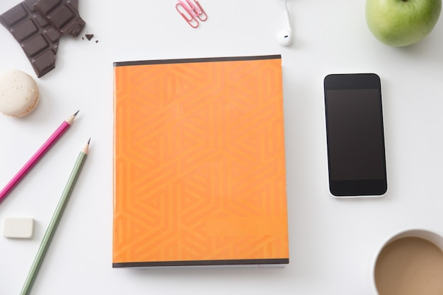 Vista superior de uma mesa de trabalho com caderno laranja