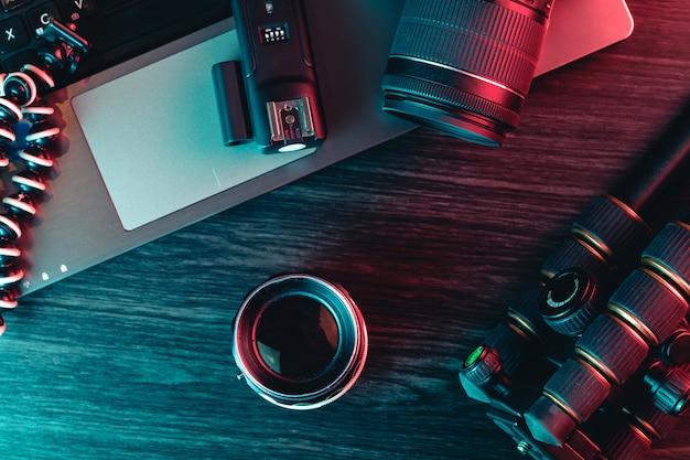 Vista superior de uma mesa de trabalho com teclado portátil, câmera moderna, lente, tripé e uma caneta
