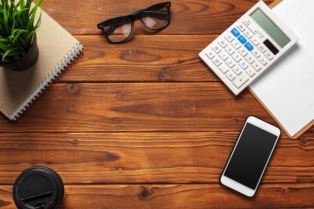 Vista superior de uma mesa de trabalho de madeira escura com material de escritório