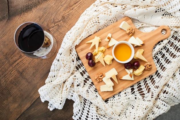 Vista superior de uma mistura de queijo parmesão, mussarela, camembert em uma tábua de madeira e um copo de vinho tinto