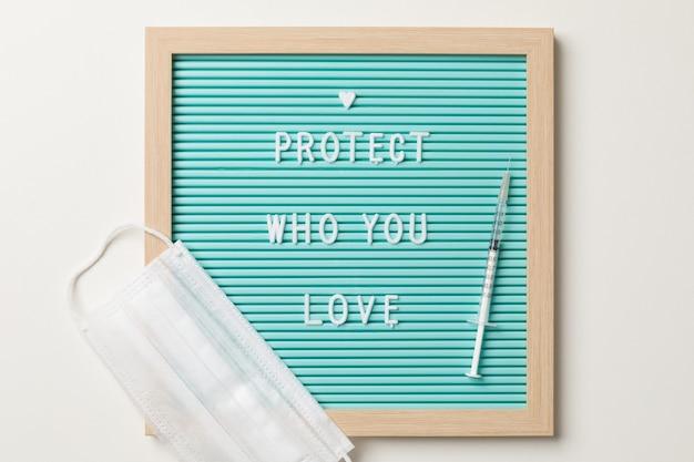 Vista superior de uma moldura com proteção de quem você ama escrito, uma máscara cirúrgica branca e uma injeção de seringa ou vacina.