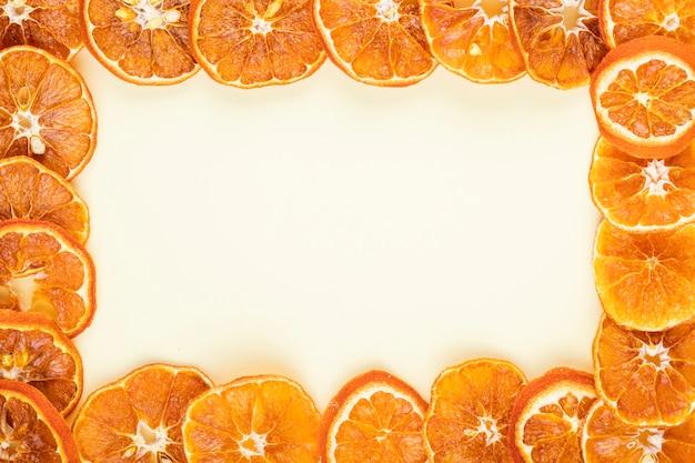 Vista superior de uma moldura feita de fatias de laranja secas, dispostas em fundo branco, com espaço de cópia