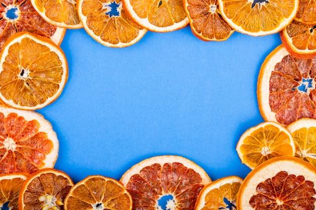 Vista superior de uma moldura feita de fatias secas de laranja e toranja, dispostas em fundo azul, com espaço de cópia